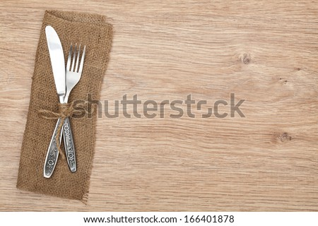 Silverware or flatware set of fork and knife on wooden table - stock photo