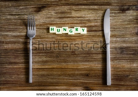 Silverware set on a wooden vintage table with sign Hungry - stock photo
