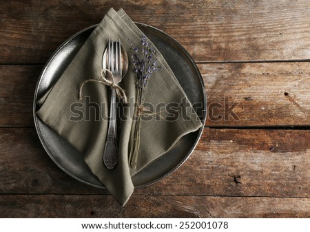 Silverware tied with rope on metal tray with burlap cloth and dried flower on wooden planks background - stock photo