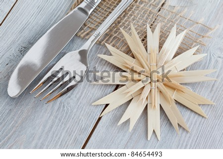 Silverware which is decorated for Christmas with a straw star on a white wooden background.
