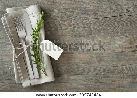 Silverware with a twig of rosemary and empty tag on rustic wooden background - stock photo