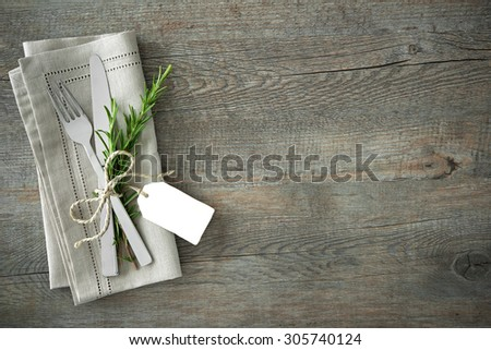 Silverware with a twige of rosemary and empty tag on rustic wooden background - stock photo
