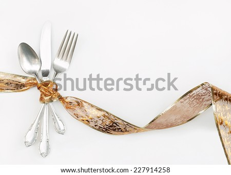 Silverware Wrapped with Holiday Gold Ribbon - stock photo