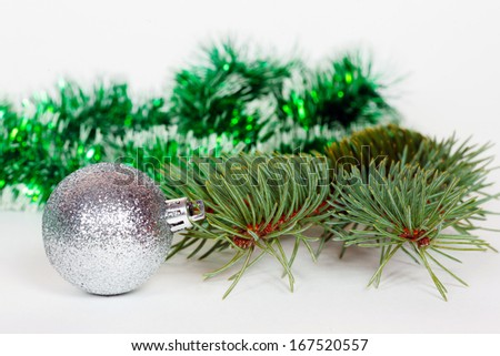 Silvery ball, pine branch and green Christmas tinsel