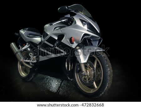 silvery sports motorcycle against dark background