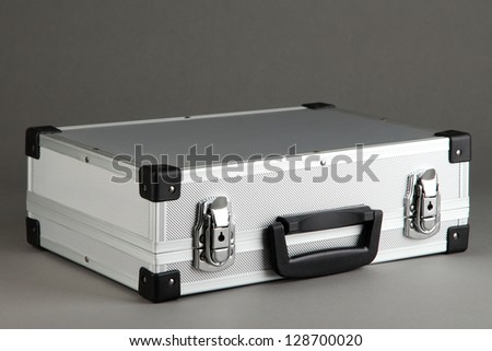 Silvery suitcase on grey background