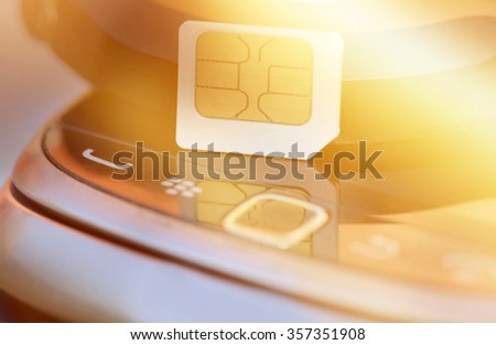 Sim card on cell phone background - stock photo