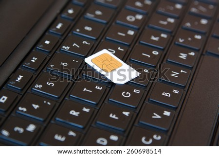 SIM card on laptop keyboard represents mobile internet. - stock photo