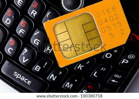 Sim card on smart phone keyboard - stock photo
