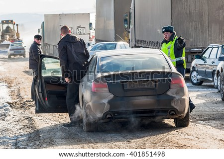 Sim, Russia - February 25, 2008: Traffic jam at interurban road caused by heavy snowstorm. The police officer has stopped the driver who tried to go round impudently all on an oncoming lane - stock photo