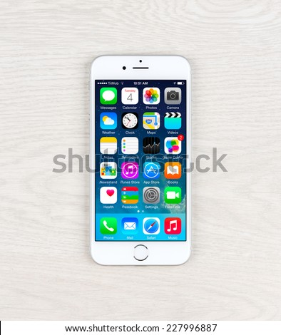SIMFEROPOL, RUSSIA - NOVEMBER 03, 2014: Apple iPhone 6 over table displaying iOS 8.1 homescreen. iOS 8 is the eighth major release of the iOS mobile operating system designed by Apple Inc.