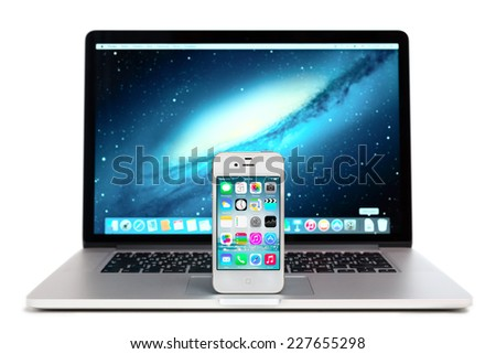 SIMFEROPOL, RUSSIA - NOVEMBER 01, 2014: Apple iPhone stay over Macbook and displaying iOS 8.1 homescreen. iOS 8.1 operating system designed by Apple Inc. Official release of October 20, 2014 - stock photo
