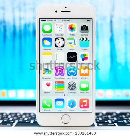 SIMFEROPOL, RUSSIA - NOVEMBER 13, 2014: Apple iPhone 6 stay over Macbook and displaying iOS 8.1 homescreen. iOS 8 is the eighth major release of the iOS mobile operating system designed by Apple Inc. - stock photo
