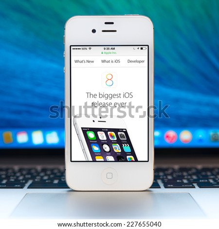 SIMFEROPOL, RUSSIA - NOVEMBER 01, 2014: Apple iPhone stay over Macbook and presenting information of iOS 8. iOS 8 is the eighth major release of the iOS mobile operating system designed by Apple Inc. - stock photo