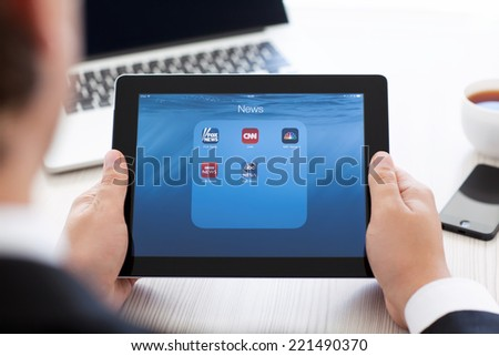 Simferopol, Russia - September 13, 2014: iPad in the hands of a businessman with popular news applications on the screen. iPad is created and developed by the Apple inc. - stock photo
