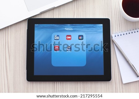 Simferopol, Russia - September 13, 2014: iPad lies on a table with popular news applications on the screen. iPad is created and developed by the Apple inc. - stock photo