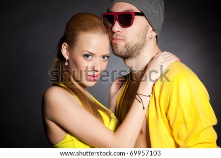 Similar color wearing young pair, horizontal isolated studio shot