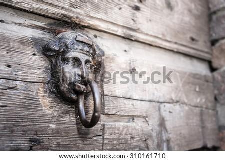 Simpel old metal door handle knocker in head shape with wooden background - stock photo