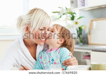 Simper mother and daughter having breakfast in the kitchen - stock photo