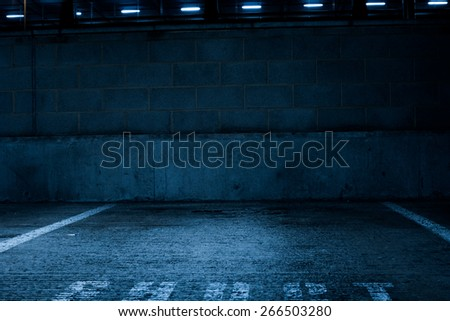 Simple Architectural Design of an Empty Rustic Concrete Car Park with Low Light Inside the Building - stock photo
