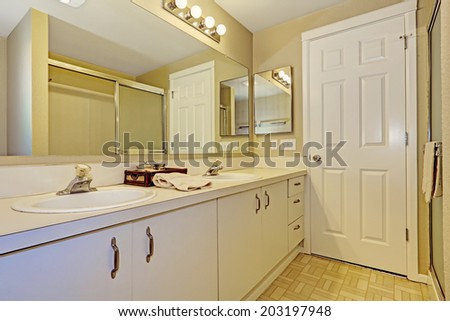 Simple bathroom interior with white cabinets and big mirror