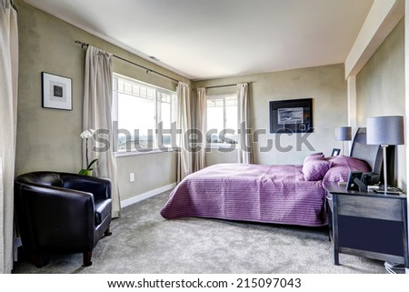 Simple bedroom interior in light grey tones with bright purple bed and leather chair
