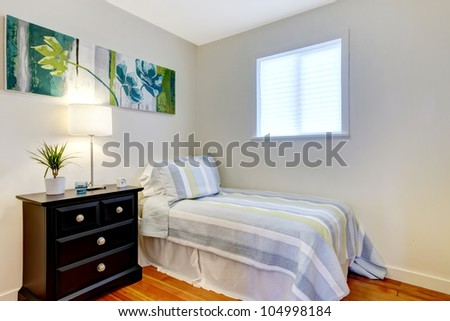 Simple bedroom with black nightstand and small bed. - stock photo