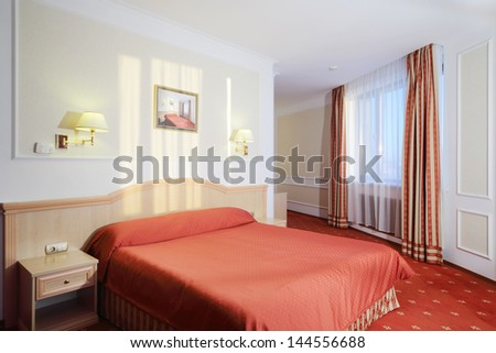 Simple bedroom with double bed with red linen, red carpet and window.