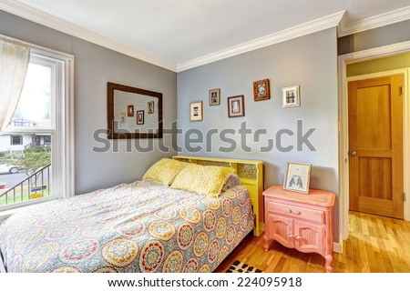 Simple bedroom with light blue walls. Bed decorated with yellow pillows. Antique pink nightstand - stock photo