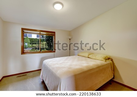 Simple bedroom with vaulted ceiling and window. Old bed with a lamp