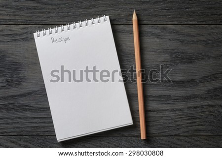 simple blank notepad with word recipe on rustic wood table, background - stock photo