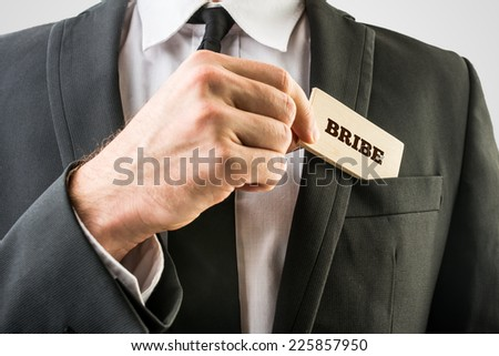 Simple Bribe Concept - Close up Businessman in Black Suit Putting Small Wooden Piece with Bribe Text in Front Suit Pocket. - stock photo