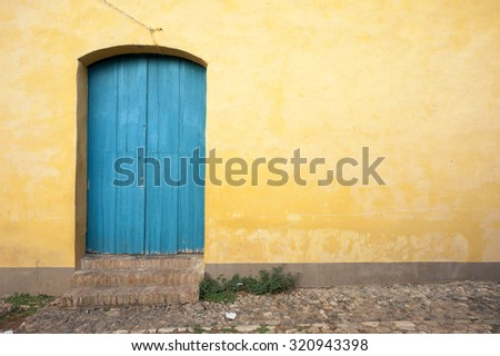 Simple brightly painted blue door in a smooth yellow ochre stucco wall on a cobblestone street in Trinidad, Cuba - stock photo