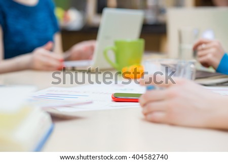 Simple Business Composition with Papers Charts and Hands holding Glass of Water making Notes gesturing typing on Computer. Focus on red Telephone in the middle of Table