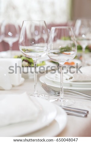 Simple but luxury rich table setting for a wedding celebration in nice cozy restaurant. Wineglasses, plates and food on a table. Sunlight from a window. Copy space