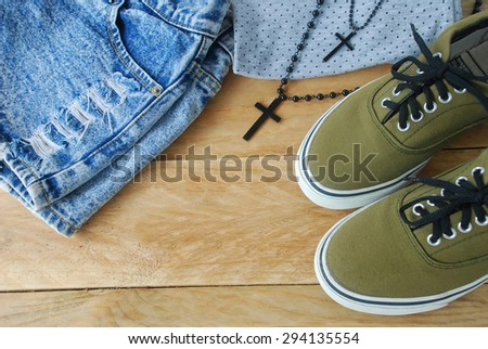 simple casual wear of young women, including gray polka dot t-shirt, black bead necklace with cross pendant, blue denim lack shorts and olive green sneakers on wooden background - stock photo