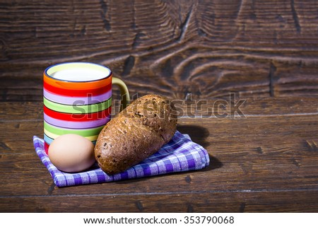 Simple country Breakfast from a mug of fresh milk with homemade rye baguette and chicken egg