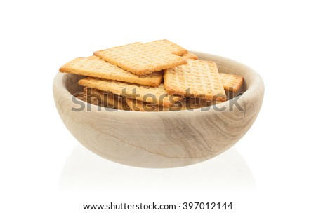 Simple crackers in a wooden bowl, isolated on a white background - stock photo