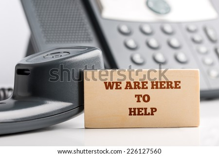 Simple Customer Support Concept Design- Close up of Small Wooden Piece with We are Here to Help Texts at the Customer Service Operator Desk with Telephone. - stock photo