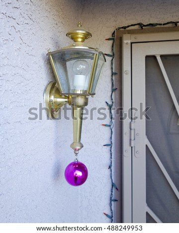 Simple decorations of house entrance with a red Christmas bauble hanging from the entrance door light; shallow depth of field