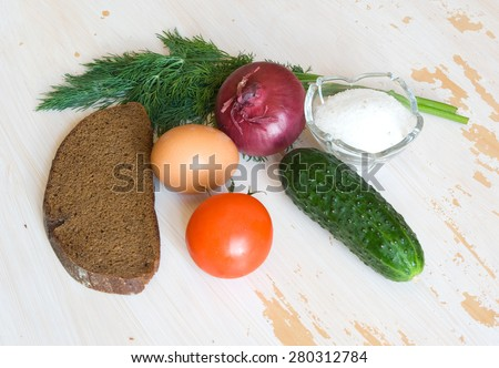 Simple farm breakfast: egg, tomato, bread, dill, red onion and salt on a painted tacky table - stock photo