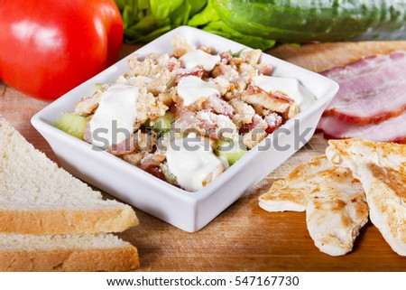 Simple, fresh salad with vegetables and meat in white bowl on a wooden board next to toast, cucumber, tomato, grilled chicken and smoked ham.