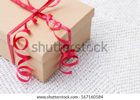 Simple gift box with red ribbon on a knitted background.