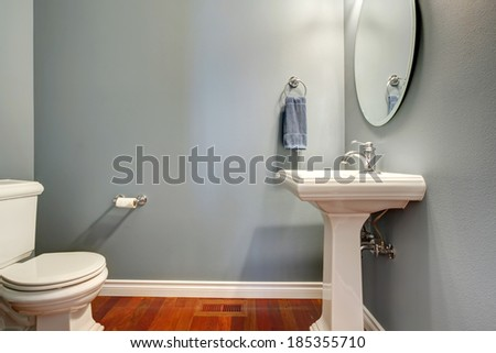 Simple grey bathroom. VIew of white toilet and washstand - stock photo