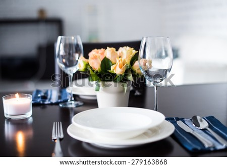Simple home table setting, glasses and cutlery, roses in a vase. - stock photo