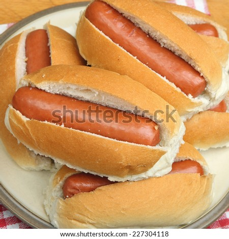 Simple hot dogs piled on a plate - stock photo