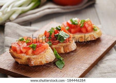 simple italian appetizing bruschetta with tomato, on old table - stock photo