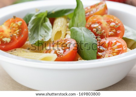 simple italian pasta penne with tomatoes and basil, close up