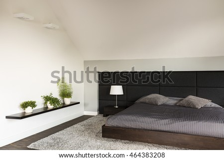 Simple light bedroom in japanese style with large bed, upholstered wall, carpet, three bonsai trees standing on a wall shelf