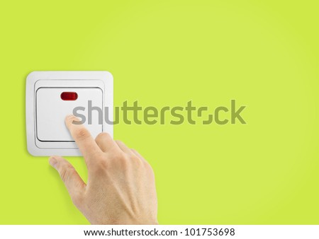 Simple light switch and hand on a green wall background - stock photo